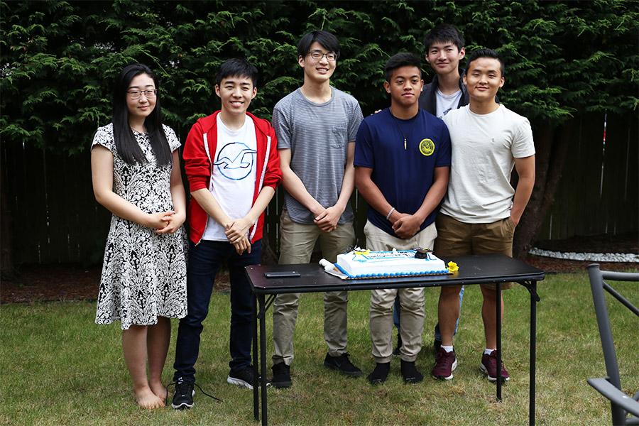 High school graduates celebrate over cake